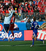 26 April 2009: Toronto FC forward Chad Barrett #19 and Kansas City Wizards goalkeeper Kevin Hartman #1 both go for the ball while Kansas City Wizards defender Jimmy Conrad #12 looks on at BMO Field in Toronto in a  game between Kansas City Wizards and Toronto FC..Toronto FC won 1-0.