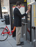 A man completes a transaction to rent a Capital Bikeshare rental bicycle in Washington DC.