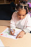 Education preschool 3-4 year olds girl drawing a picture of a house using marker