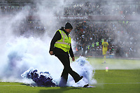 A West Ham safety steward reacts to a flare thrown onto the pitch and enters the field of play and proceeds to kick the flare to a safer place away from the playing surface during West Ham United vs Brentford, Premier League Football at The London Stadium on 3rd October 2021