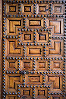 A heavy wooden door is studded with star shaped metal motifs, Parador hotel, Hostal dos Reis Catolicos
