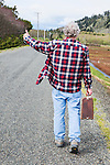 Senior man with suitcase walks a back road amid cranberry farms.  Near Graylend Beach, State Park, Tokeland Beach, on the central Washington Paciific Coast south of Westport, is flooded by rain making for an unusual landscape of water in the sand dunes.