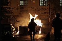 Pictured: A riot police officer's silhouette against burning wheelie bins in Exarchia, central Athens Tuesday 02 December 2014<br /> Re: At least 15 people have been arrested after a peaceful support rally for jailed hunger strike anarchist turned into violent confrontation with police. Authorities used tear gas and stun grenades to quell rioters carrying Molotov cocktails.<br /> As an estimated between 8,000 and 10,000 protesters marched through the central Athens shouting slogans in support of Nikos Romanos, the imprisoned anarchist who is staging a hunger strike as he demands the right to be able to attend university, anarchists' march got violent on the streets of Exarchia, downtown Athens.