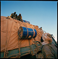 Sahara desert, Libya-Chad, November/December 2004..Every week, a convoy of 40 privately owned Libyan trucks loaded by the WFP with about 1000 metric tons of western food aid cross 2500 km of deep desert across Libya and Chad to reach more than 200 000 refugees from Darfur in camps near the Sudanese border. Gasoil for 6000 km is carried atop each truck...there is no gas station in the desert...