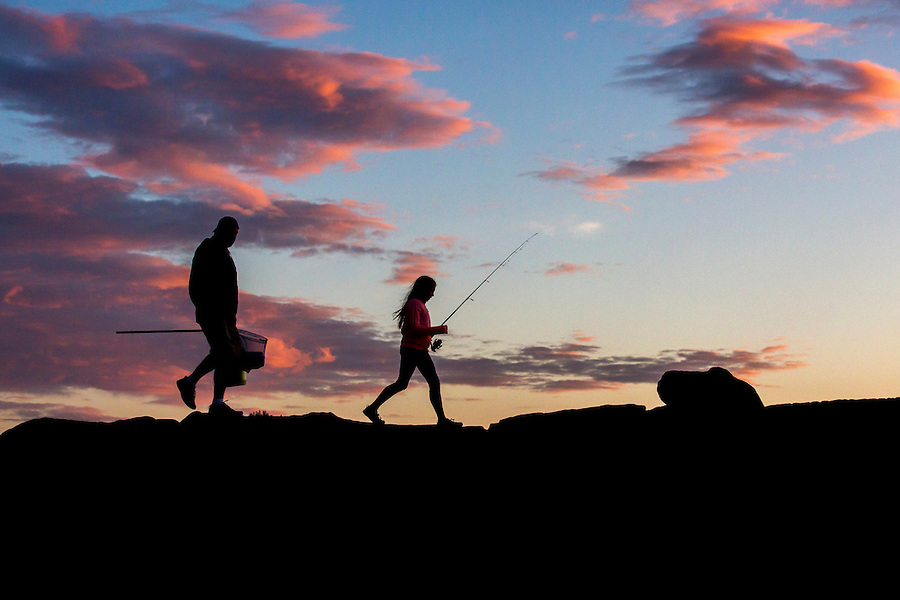 A father and daughter head out on a jetty to go fishing.