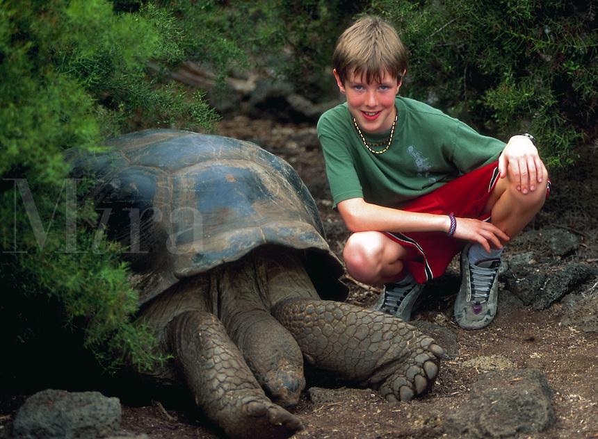 Kid with giant tortoise at Darwin Research Center, Galapagos Islands, Ecuador