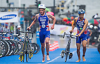 26 AUG 2012 - STOCKHOLM, SWE - Jonathan Brownlee (GBR) of Great Britain (left) leads Vincent Luis (FRA) of France (right) through transition at the end of their bike leg during the 2012 ITU Mixed Relay Triathlon World Championships in Gamla Stan, Stockholm, Sweden .(PHOTO (C) 2012 NIGEL FARROW)