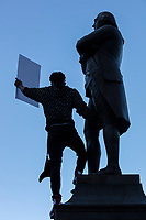"""Azarius Rivera, 23, holds a sign reading """"Trump/Pence Out Now"""" as he stands atop the statue of Samuel Adams outside Faneuil Hall at the end of the 2020 Women's March protest in opposition to the re-election of US president Donald Trump in Boston, Massachusetts, on Sat., Oct. 17, 2020."""