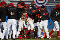 Batavia Muckdogs shortstop Marcos Rivera (8) emerges from the celebration at home plate after hitting a three run walk off home run in the bottom of the ninth inning during a game against the West Virginia Black Bears on June 25, 2017 at Dwyer Stadium in Batavia, New York.  Batavia defeated West Virginia 4-1 in nine innings of a scheduled seven inning game.  Rony Cabrera is lifting Rivera's jersey as Jhonny Santos (13) looks on.  (Mike Janes/Four Seam Images)