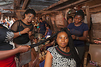 Nigeria. Enugu State. Enugu. Ogbete Main Market. Hairdresser shop. A group of women is making braids of hair to a black african woman. The customer is seated on a chair and waits calmly. Enugu is the capital of Enugu State, located in southeastern Nigeria. 2.07.19 © 2019 Didier Ruef
