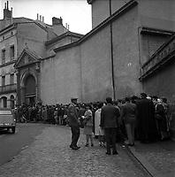 """Affaire de la """"Tournerie des drogueurs""""  JUIN 1961<br /> <br /> Devant le Palais de Justice, rue des Fleurs. 5 juin 1961. Vue d'ensemble de la file d'attente des personnes venues assister au procès (vue de dos). Cliché pris dans le cadre de l'affaire de la """"Tournerie des drogueurs"""" dont le procès s'est ouvert à Toulouse le 5 juin 1961. Observation: Affaire de la """"Tournerie des drogueurs"""" : Procès qui s'est ouvert aux assises de Toulouse le 5 juin 1961, sous la présidence de M. Gervais (conseiller doyen). Sur le banc des accusés se trouvent François Lopez, Raoul Berdier, Marie-Thérèse Davergne (Maïté) et d'autres malfaiteurs toulousains (Camille Ajestron, Henri Oustric, Raymond Peralo, Marcel Filiol, Paul Carrère, Charles Davant et François Borja). Outre les accusations pour association de malfaiteurs, ils comparaissent pour l'assassinat de Jean Lannelongue, propriétaire du Cabaret la Tournerie des Drogueurs (rue des Tourneurs) dans la nuit du 3 au 4 janvier 1959, au cours d'une tentative de racket."""