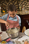 3 year old boy in kitchen at home learning to cook, baking, stirring batter in bowl