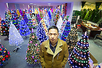 November 28, 2015, Yiwu, China - Reng Guoan (English name Raven) General Manager of Sinte An Christmas tree factory sits in his factory showroom. His company makes one million artificial trees a year for export and around 100,000 of those go to the UK.Photo by Dave Tacon / Sinopix