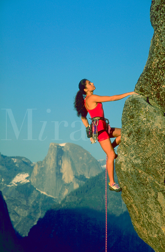 Woman climbing a rocky outcropping in Yosemite Valley, California with mountains and blue sky in the background.