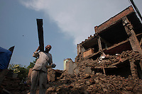 A man collects items from hir destroyed house in Shanku, near Kathmandu, Nepal. May 9, 2015