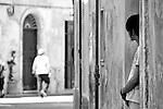 """Lecce - Zona Giravolte - L'integrazione ha trovato anche qui la propria """"casa"""". Un giovane cinese osserva il passaggio delle persone sulla strada - Progetto """"Margini"""""""
