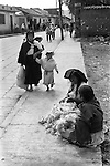 San Cristobal de las Casas  Mexico 1973 Indigenous native indian women and children selling sheep's wool at the side of the road, mother and children going to the daily market. Mexican state of Chipas 1970s
