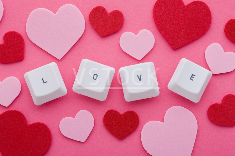 """Computer keys arranged in word """"love""""  and pink and red hearts"""