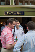 Young men drink outside a bar in the City of London