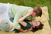 Young couple embracing on blaket in the grass