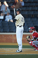 Shane Muntz (11) of the Wake Forest Demon Deacons looks to his third base coach for the signs during the game against the Gardner-Webb Runnin' Bulldogs at David F. Couch Ballpark on February 18, 2018 in  Winston-Salem, North Carolina. The Demon Deacons defeated the Runnin' Bulldogs 8-4 in game one of a double-header.  (Brian Westerholt/Four Seam Images)