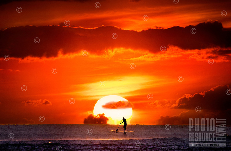 Apaddle boarderenjoying a memorable sunset.