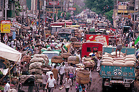 In Calcutta, India, anything goes as to parking and shopping in the crowed conditions. trucks, people, shopping, cityscape. congestion on city streets. Calcutta, India traffic condidtions, street scene.