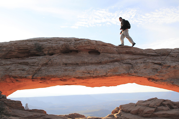 Man at Mesa Arch at sunrise, Island in the Sky area, Canyonlands National Park, Utah, USA. .  John offers private photo tours in  Canyonlands National Park and throughout Utah and Colorado. Year-round.