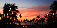 Colorful pool and Pacific Ocean sunset with palm tree silhouettes and iconic Hawaiian fire torches in the foreground, on the Big Island of Hawaii