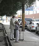 MAN AND SON ENTERTAINS CARS AT BORDER CROSSING IN MEXICALI
