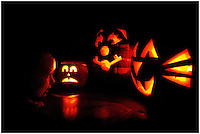 Jack-o-lanterns for Halloween. A young boy peers into three carved pumpkins on Halloween night. Model released.