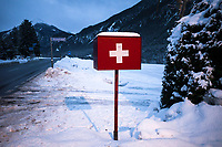 Switzerland. Canton Graubünden. Surava. Albula asphalt  road. Mailbox with the swiss flag. The flag of Switzerland displays a white cross in the centre of a square red field. The white cross is known as the Swiss cross. Snow on the fields and on the Alps mountains. Surava is part of the municipality Albula/Alvr. 29.12.2020 © 2020 Didier Ruef