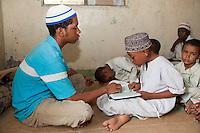 Zanzibar, Tanzania.  Imam Helping Young Boy in a Madrassa (Koranic School) Read Verses in the Koran.