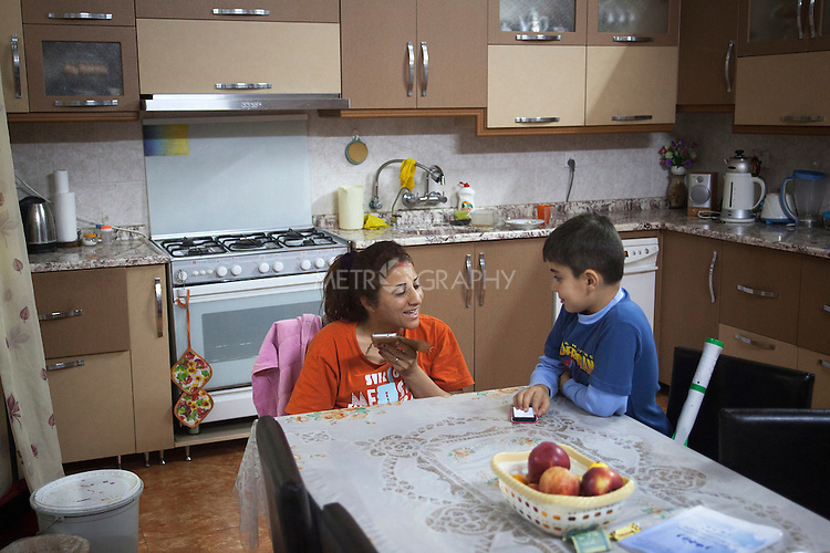 30/10/14. Erbil, Iraq. Milad (right) listens to his aunt Susan speak to her husband Amir by phone, as he buys chicken for a farewell party being held for the brothers. Milad and Wassam will return to the orphanage in Alqosh the next day and start the new school year.
