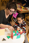 Education Preschool 3-4 year olds SEIT working with boy in classroom, building with magnet tiles
