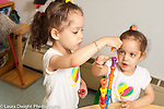Education Preschool 3 year old identical twin girls using opposite hands to build peg tower