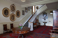 A collection of family portraits lead up the stairs from the entrance hall