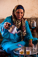Ksar Elkhorbat, Morocco.  Middle-aged Amazigh Berber Woman Pouring Tea in her Living Room.
