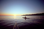 Baja, Mexico, Sea Kayaking, Female sea kayaker paddles beyond bow kayak toward sunrise, Sea of Cortez, Gulf of California, Baja Sur,