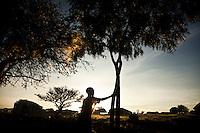 A girl shaking dew froma tree  in Madi Opei, Uganda.