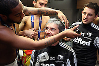 Pictured: Coach Oscar Garcia (FRONT) has his hair cut by Swansea players Kemy Agustien (L) and Chico Flores (C) in the team changing room after the end of the game. Sunday 24 February 2013<br /> Re: Capital One Cup football final, Swansea v Bradford at the Wembley Stadium in London.