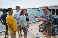 Professor Hinrich Kaiser speaks to students Jester Ceballos, Eric Leatham, Caitlin Sanchez, and Scott Heacox on a boat in the harbor at Dili, Timor-Leste (East Timor)