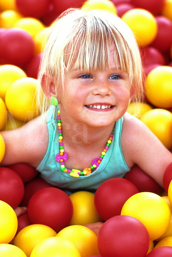 Young girl age 4 smiling portrait at camera in McDonalds balls playgroun