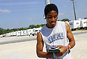 Fifteen-year-old Michael Lewis hangs out at the basketball court, listening to rap music during a school day at Renaissance Village in Baker, Louisiana, May 19, 2006.<br />(Cheryl Gerber for New York Times)