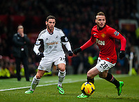 Saturday 11 January 2014 Pictured: Alvaro Vasquez looks on as Alexander B?ttner  takes the ball forwards for Manchester United<br /> Re: Barclays Premier League Manchester Utd v Swansea City FC  at Old Trafford, Manchester