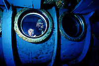 Tourists peer through the viewing portholes of the Atlantis submarine eager to see Hawaii's unique marine life. This photo taken off the coast of Waikiki near the sunken ship YO257.