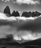 The Towers of Paine peek through the clouds.