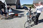 """Foto: VidiPhoto<br /> <br /> KESTEREN – Een doedelzakspeler, een burgemeester, twee dominees, twee kalfjes, drie tractoren, vijf aanspanningen met paard, een menwagen op aanhanger, bakfietsen en tientallen versierde auto's zorgden voor een waar spectakel in de polder. Massaal trokken ze donderdagmiddag over het boerenerf van het vijftigjarige echtpaar Jan en Ita (beiden 73) van Zetten uit Kesteren (Gld). Omdat een uitbundig boerenfeest nog niet mogelijk is, bedachten de kinderen en kleinkinderen een """"Felicitatie Drive-In"""". Vrienden, familieleden en collega's werden uitgenodigd om aan het eind van de middag via het erf aan te komen rijden om op zo ludiek mogelijke wijze het bruidspaar op gepaste afstand te feliciteren. Dat gebeurde. Het gouden echtpaar woont nog op de melkveehouderij die ze inmiddels aan een van hun  zoons en zijn vrouw hebben overgedaan. Alleen de oudste zoon, die een boerderij in Denemarken heeft, mocht er vanwege de coronamaatregelen niet bij zijn."""