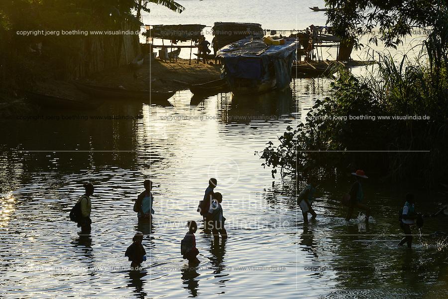 MADAGASCAR, village AMBOHITSARA at canal des Pangalanes, tribe ANTAMBAHOAKA, children on the way home from school / MADAGASKAR, Mananjary, Dorf AMBOHITSARA am canal des Pangalanes,  Volksgruppe ANTAMBAHOAKA, Schulweg durchs Wasser