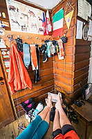 A ski tour through the Pirin Mountains of Bulgaria. Inside the Tevno Ezero Hut a couple dries out their ski gear and warms up next to a heater.